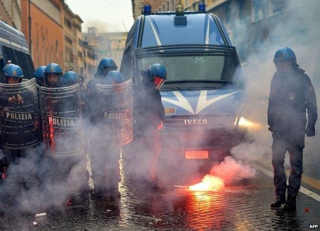 A policeman clears away a flare during a confrontation with students in Rome, 15 November