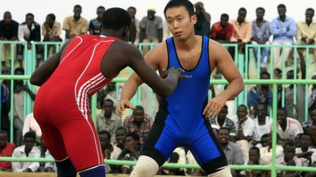 "Japanese diplomat Yasuhiro Murotatsu (R), known as ""Muro"" in the ring competes against Sudanese fighter Saleh Omar Bol Tia Kafi, nicknamed ""Al-Mudiriya"" in a traditional Sudanese wrestling match on 28 August 2013"