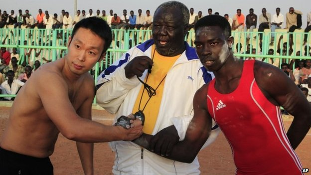 Sudanese wrestler Saleh Omar and Japanese diplomat Yasuhiro Murotatsu shake hands before their friendly match in the Haj Yousif neighbourhood - 25 October 2013