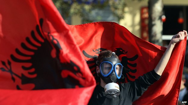 An Albanian environmental activist wears a gas mask and holds up a national flag as he takes part in a protest in front of the Albanian parliament in Tirana (14 November 2013)