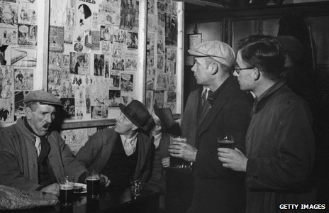 Men drinking and looking at cartoons in a pub - part of the Mass Observation project