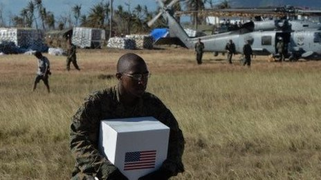 A US Marine loads supplies bound for typhoon victims onto a helicopter.
