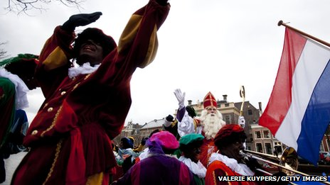 Sinterklaas, surrounded by 'Black Peters' and the Dutch flag