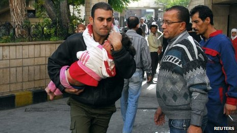 A man carries a child injured in a bomb attack outside the former Hijaz railway station in central Damascus (6 November 2013)