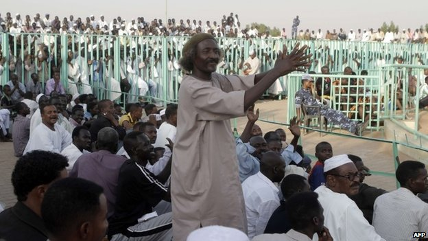 A supporters applauds during a traditional Sudanese wrestling match on 25 October 2013 at a stadium in Khartoum, Sudan