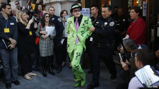 A man dressed as The Riddler is taken away by a San Francisco police officer after being apprehended by five-year-old leukaemia survivor Miles dressed as Batkid in San Francisco on 15 November 2013