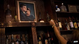 A bartender places a candle near a portrait of John F. Kennedy and Jacqueline Kennedy is seen in the Kennedy Room bar in Dallas 9 October 2013