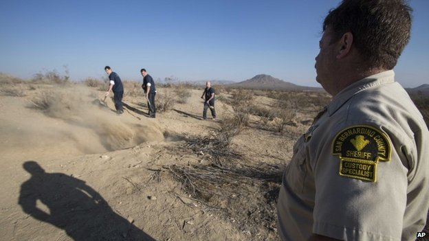 San Bernadino County Sheriff's Department Custody Specialist Ray Lovell keep watches as the workers fill the two shallow graves at the site on the outskirts of Victorville that contained the skeletal remains of members of missing McStay family  15 November 2013
