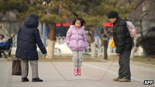 Chinese girls jumps over a skipping rope held by her parents