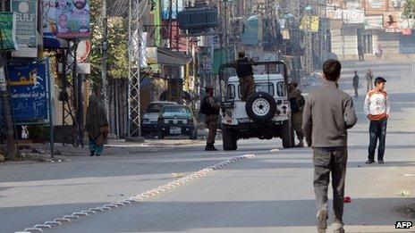 Pakistani soldiers keep watch during a curfew in Rawalpindi on 16 November 2013.