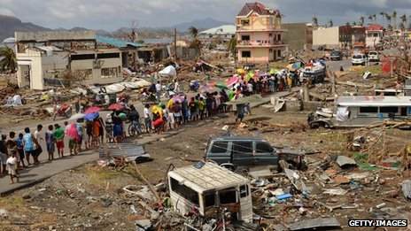 Survivors form a queue to receive relief goods at a devastated coastal area on November 16, 2013 in Leyte, Philippines.