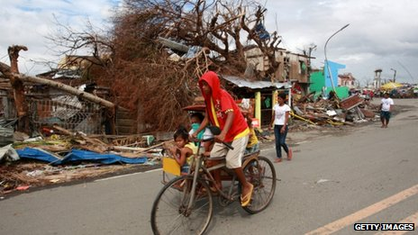 People travel past debris caused by Typhoon Haiyan in Tanauan, Leyte, 16 November