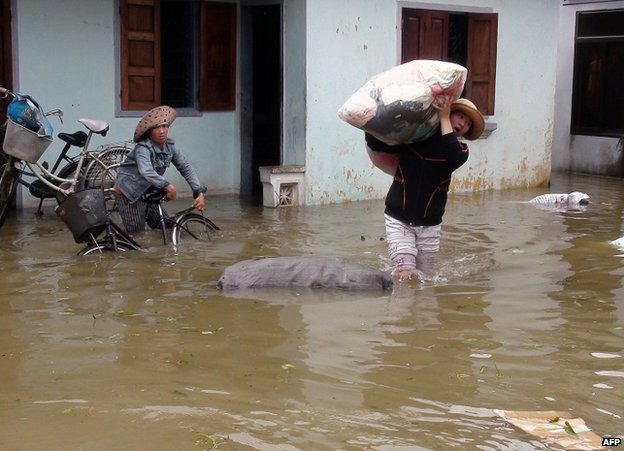 Residents rescue their belongings from a flooded house in Qui Nhon city, Binh Dinh province, Vietnam, 16 November