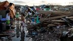 Family stands among rubble in the Philippines