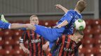 Cathal Beacom of Ballinamallard United competes for the ball against Crusaders opponent Matthew Snoddy