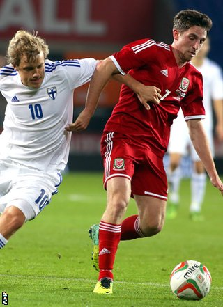 Joe Allen of Wales holds off the challenge of Teemu Pukki of Finland