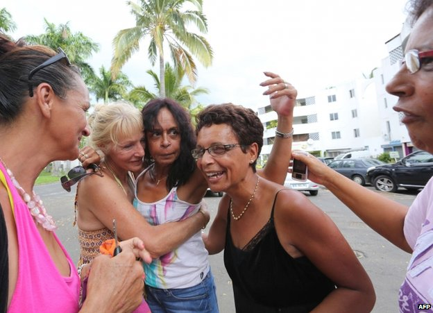 Francis Collomp's wife Anne-Marie (centre) celebrates news of her husband's freedom with relatives on the French Indian Ocean island of Reunion, 17 November