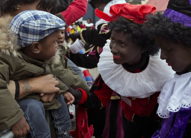 Black Pete revellers in costume meet a family in Amsterdam, 17 November