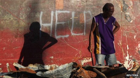 "A man, standing in front of a wall on which the word ""help"" is written, examines a pile of debris"