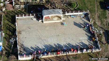 "An aerial photograph of a group of people who have written ""help please"" on a patch of concrete to be seen from the air"
