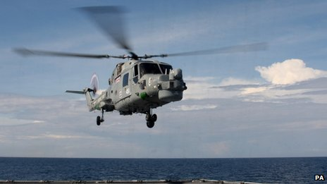 A helicopter hovers above the deck of HMS Daring