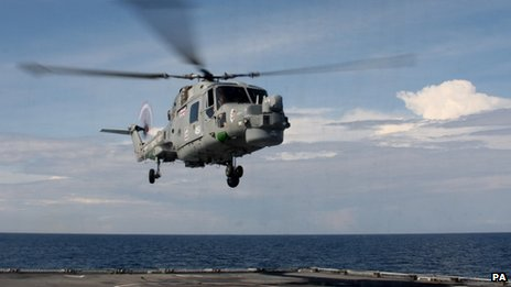A Lynx helicopter hovers above the deck of HMS Daring