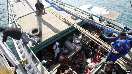 File photo: Iranian asylum seekers who were caught in Indonesian waters while sailing to Australia sit on a boat at Benoa port in Bali, Indonesia, 12 May 2013