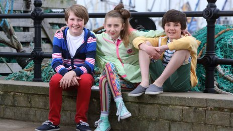 Sam Hattersley, Olivia Cosgrove and Ryan Wilkinson from CBBC's All At Sea sit against a wall