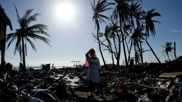 Boy standing among debris of homes in Tacloban, Philippines, after Typhoon Haiyan