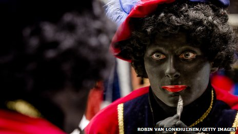 An actress applies black make-up to her face