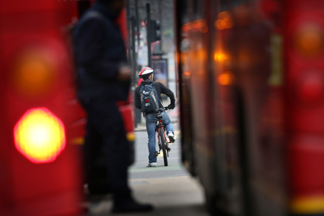 Cyclist between buses