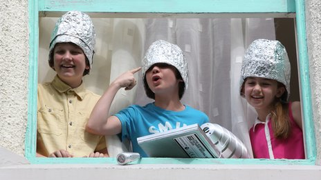 The three main characters of CBBC show All at Sea wearing foil hats and looking out of a window