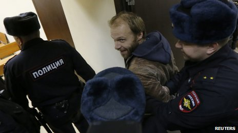 Photographer Denis Sinyakov (C) of Russia, one of the 30 people who were arrested over a Greenpeace protest at the Prirazlomnaya oil rig, is escorted before a court session in St. Petersburg, November 18, 2013