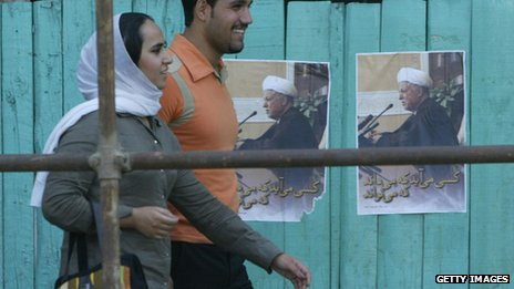 Iranians walking past campaign posters