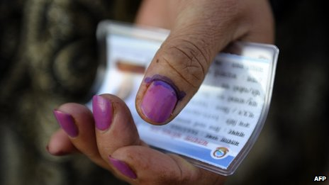 A Nepalese woman shows her finger after election officials marked it with indelible ink at a polling station in Kathmandu on 19 November 2013