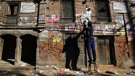 A Nepalese policeman removes election campaign posters from a wall near a polling booth in Bhaktapur, Nepal, 18 November 2013