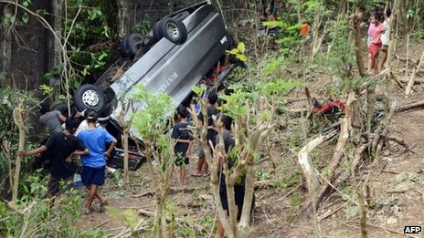 People look at the wreckage of a tourist bus one day after it plunged into a ravine in Uluwatu on Indonesia's resort island of Bali on 19 November 2013