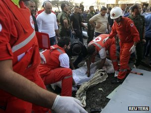 Red Cross workers recover a body from the scene of the explosions in Beirut