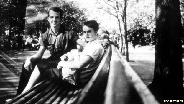 Lee Harvey Oswald and his wife on a park bench, with baby
