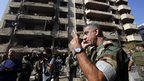 A member of the Lebanese army talks on the phone at the site of a blast in Bir Hassan neighbourhood in southern Beirut, 19 Nov