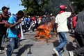 People circle a burning road block during protests in Port-au-Prince