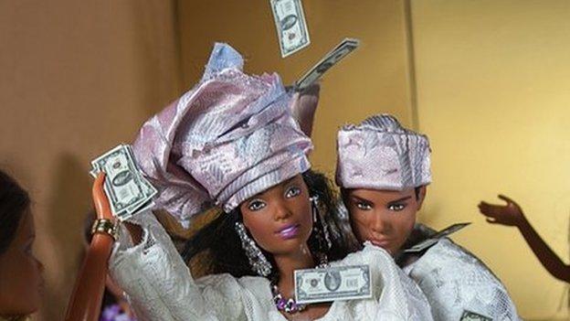 Barbie dolls being sprayed with money at wedding