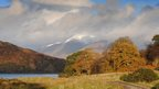 A snow capped mountain can be seen amongst cloud. In the foreground are trees and hillsides in autumn colours and part of a loch can be seen.