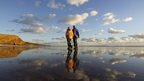 A man, woman and small dog are walking on wet sand. The blue sky and clouds above are reflected in the water on the ground.