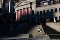 A man sits on the steps of the Vancouver Art Gallery as the sun sets in British Columbia