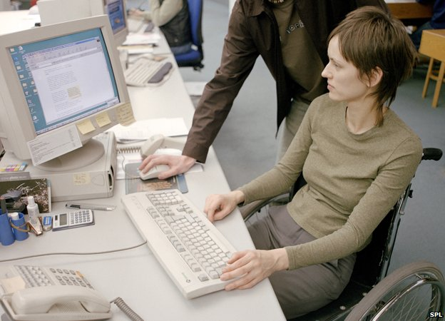 Woman in wheelchair and standing man look at computer screen. Posed photograph