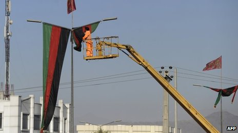 An Afghan municipality worker hangs a flag near the premises where the forthcoming Loya Jirga will be held (19 November 2013)