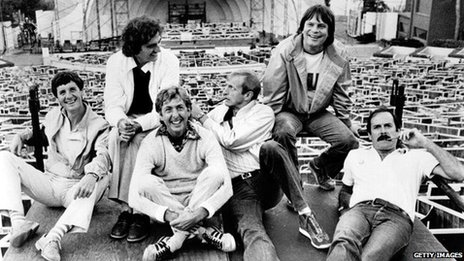 Monty Python including (left to right) Michael Palin, Terry Jones, Eric Idle, Graham Chapman (1941 - 1989), Terry Gilliam, and John Cleese, lounge at the site of their filmed live show at the Hollywood Bowl, Hollywood, California, 1982