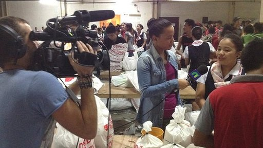 Leah filming in Cebu with volunteers packing supplies for victims of Typhoon Haiyan