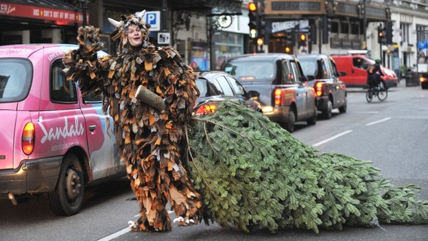 Man in costume drags a tree